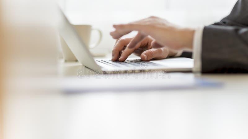 Close up das mãos do homem de negócios usando o laptop foto de stock royalty free