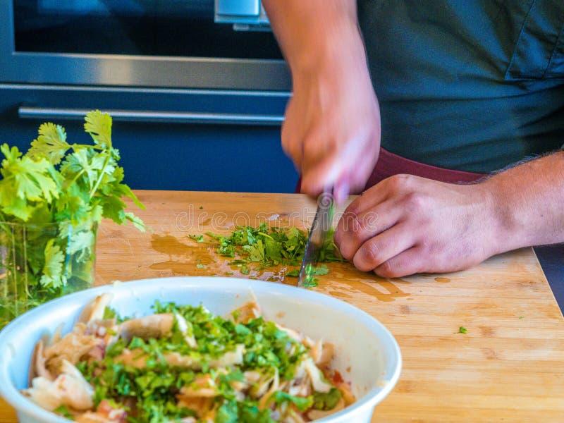 Close-up das mãos do homem que preparam vegetais e fruto na culinária moderna imagens de stock