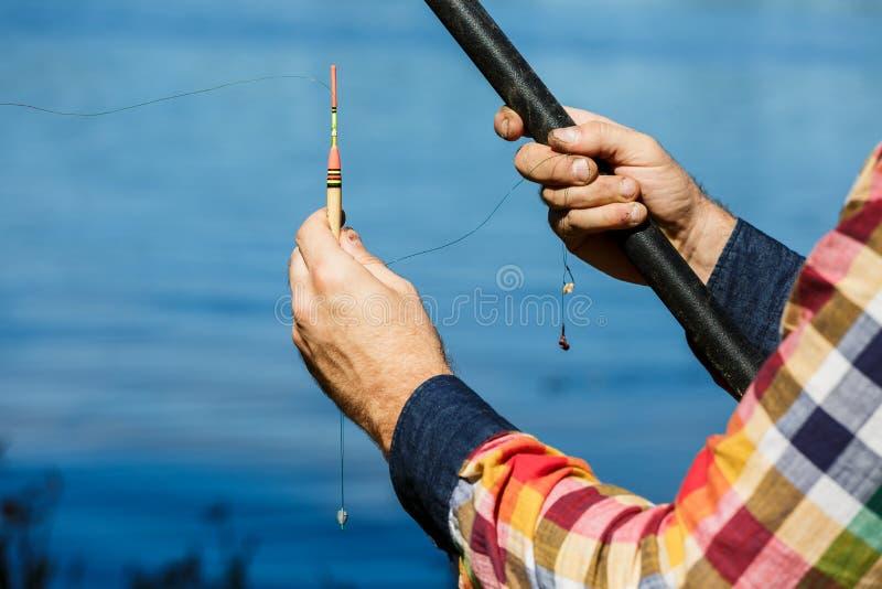 Close-up das mãos do pescador Pescador que guarda um polo de pesca, um bobber e um gancho imagens de stock royalty free