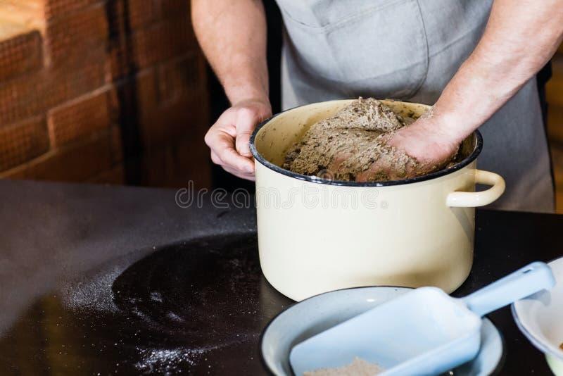 Close up das mãos dos homens para amassar a massa para o pão foto de stock royalty free