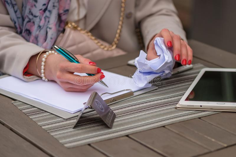 Close-up das mãos fêmeas Escrita da mulher algo que senta-se no caf fotografia de stock