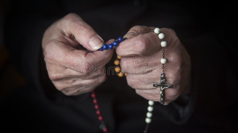 Close up das mãos fêmeas velhas que rezam com rosário foto de stock