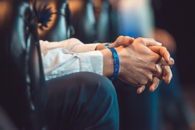 Close-up das mãos masculinas abraçadas que sentam-se em uma cadeira de couro o orador está esperando sua volta no negócio foto de stock royalty free