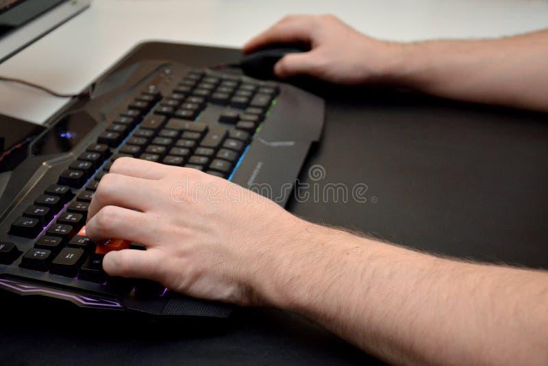 Close-up das mãos masculinas em um teclado preto do jogo com luz de néon em uma tabela preta Vista lateral imagem de stock royalty free