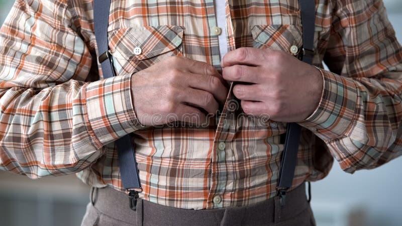 Close up das mãos masculinas que abotoam-se acima da camisa quadriculado, roupa antiquado fotografia de stock royalty free