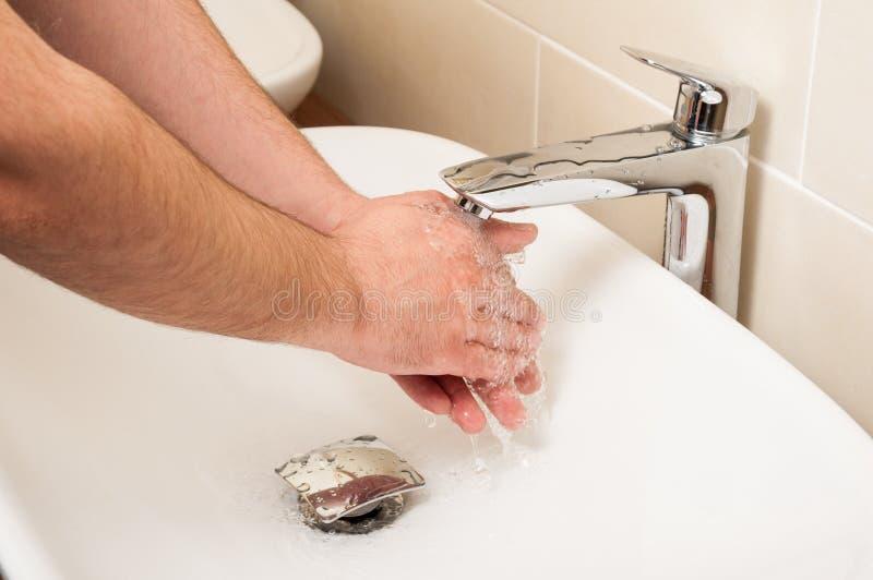 Close up das mãos masculinas que estão sendo lavadas no dissipador branco fotografia de stock