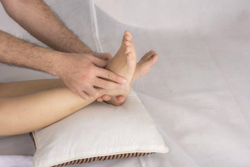 Close-up das mãos masculinas que fazem a massagem do pé imagem de stock