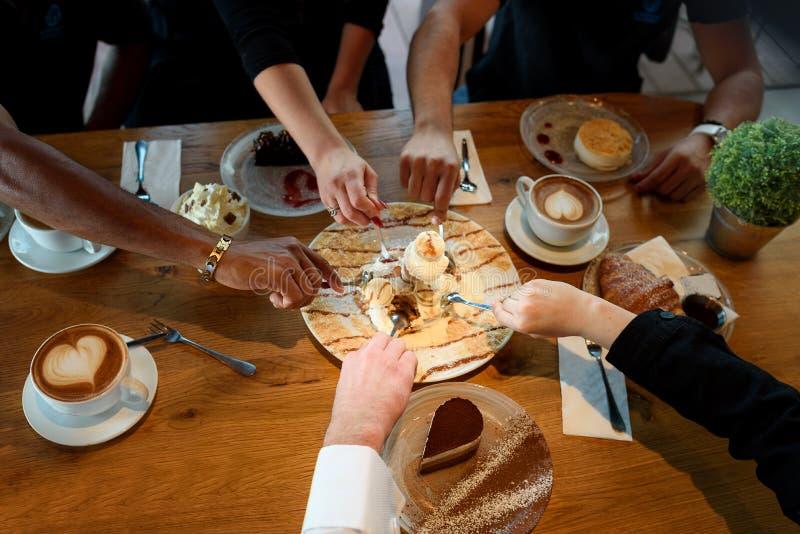 Close up das mãos multirraciais com sobremesas e copos de café em um café foto de stock royalty free