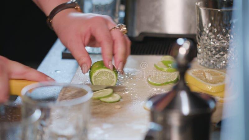 Close-up das mãos que cortam um cal na cozinha fotos de stock