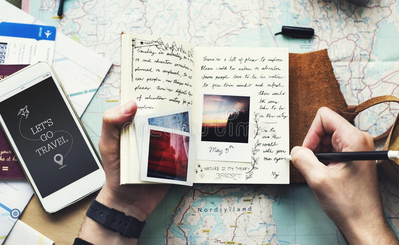 Close up das mãos que guardam o caderno do diário da viagem sobre o backgro do mapa fotografia de stock royalty free