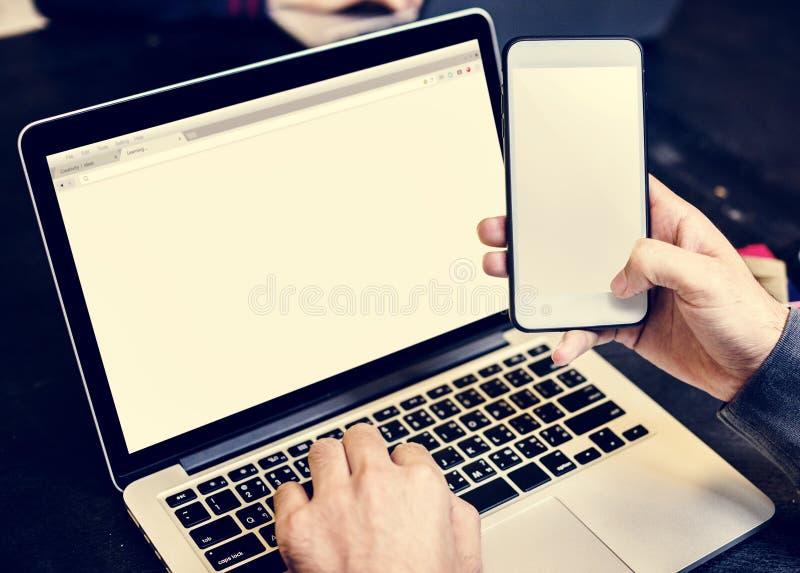 Close up das mãos que guardam o telefone celular com fundo do portátil do computador fotografia de stock royalty free
