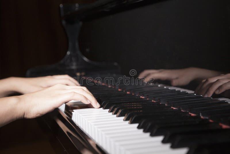 Close-up das mãos que jogam o piano imagem de stock