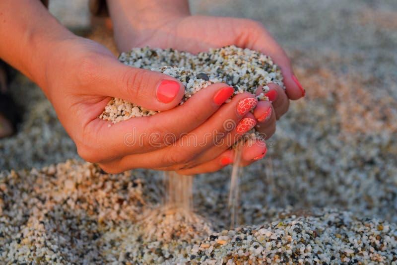 Close-up das m?os que liberam a areia deixando cair Areia que corre atrav?s das m?os fotos de stock royalty free