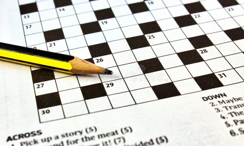 Close up das palavras cruzadas de um jornal com um lápis de ligação preto e amarelo fotografia de stock royalty free