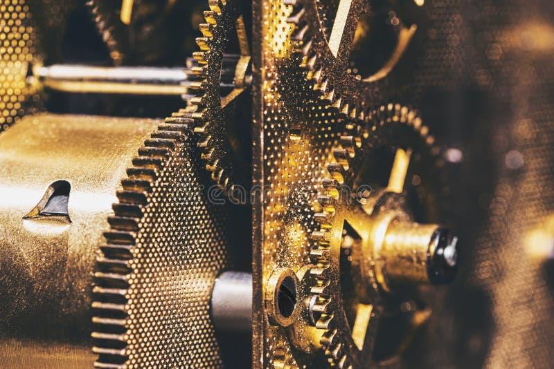 Close up das rodas denteadas ou das engrenagens em um maquinismo de relojoaria, fundo dourado fotos de stock