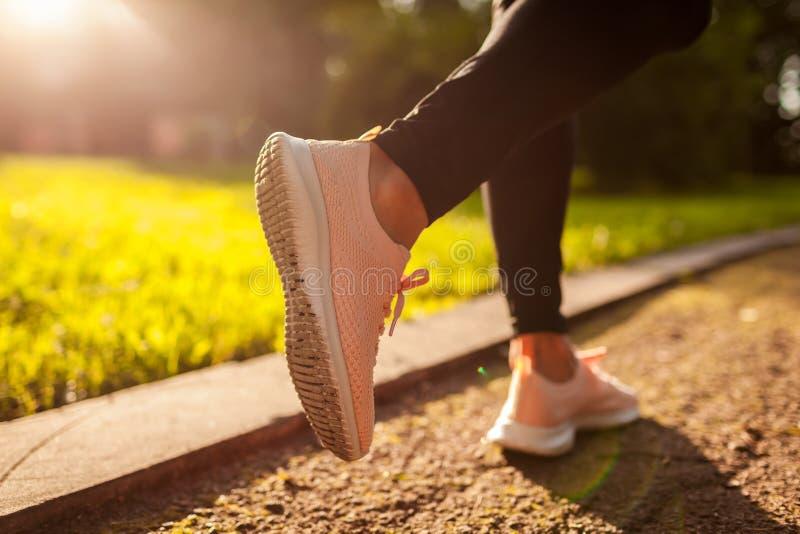 Close up das sapatilhas Mulher desportivo nova que corre no parque do verão Movimentar-se do desportista imagens de stock royalty free