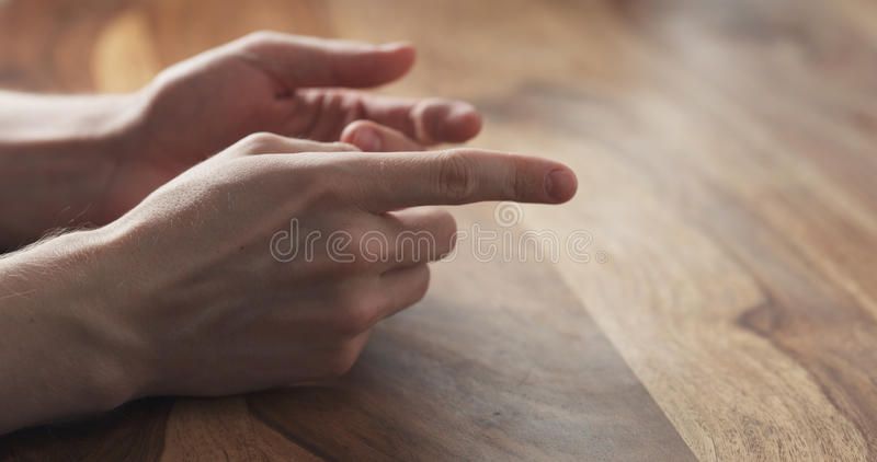 Close up das sugestões dos gestos de mãos do homem novo na reunião foto de stock