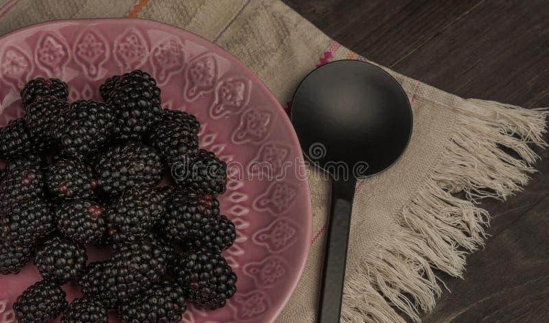 Close-up de amoras-pretas frescas em uma bacia na tabela rústica imagem de stock