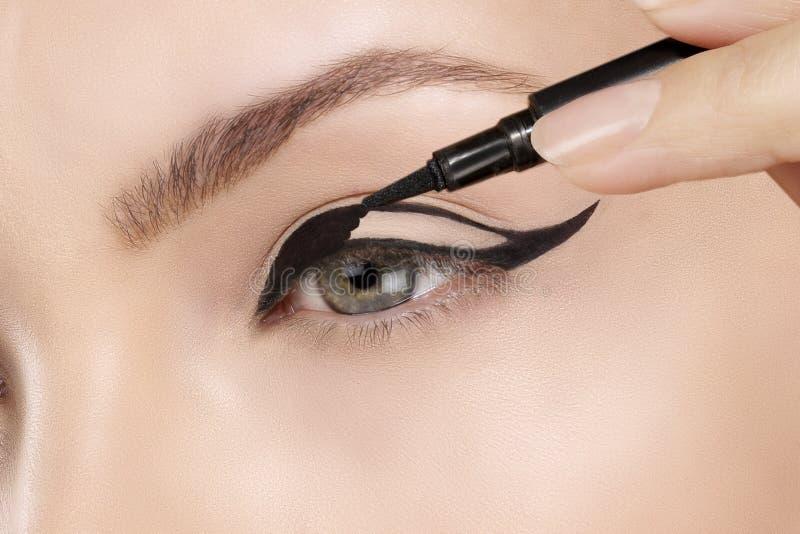 Close up de aplicação modelo bonito do lápis de olho no olho fotos de stock royalty free