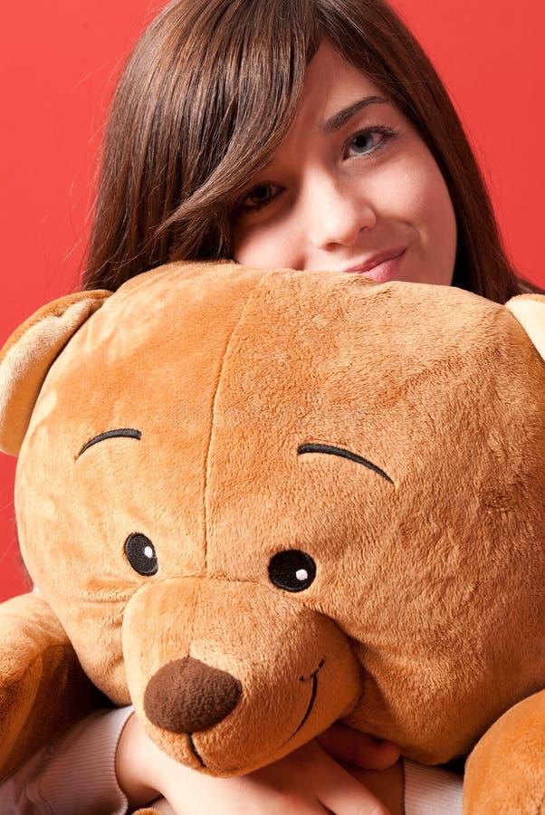 Close-up de assento do urso de peluche do abraço da mulher nova foto de stock