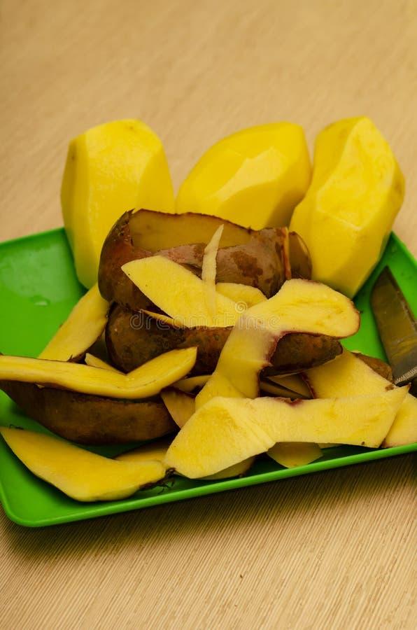 Close-up de batatas descascadas em uma placa com um fundo macio fotografia de stock royalty free