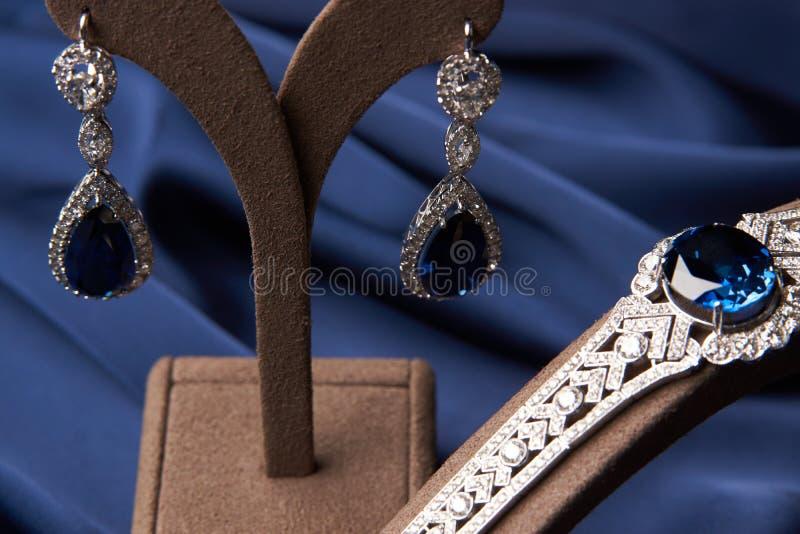 Close-up de brincos bonitos e de bracelete de uma platina fotografia de stock