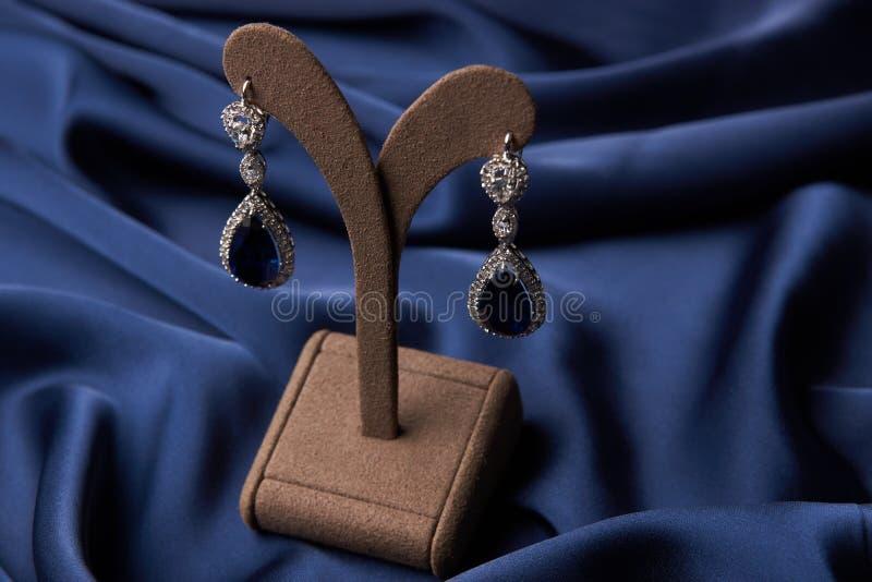 Close-up de brincos bonitos e de bracelete de uma platina foto de stock