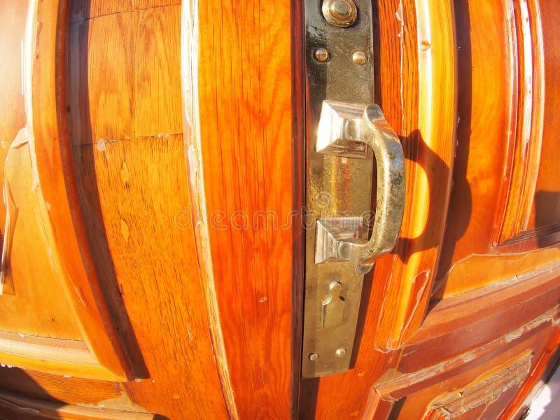 Close-up de bronze velho do puxador da porta em uma porta vermelha de madeira fotos de stock