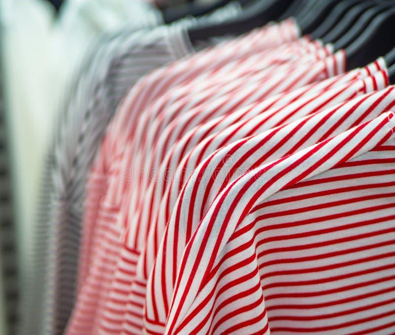 Close up de camisas de algodão listradas da mulher em ganchos na loja foto de stock