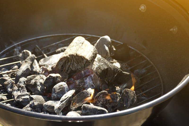Close up de carv?es e de madeira ardentes em uma grelha da grade fotografia de stock