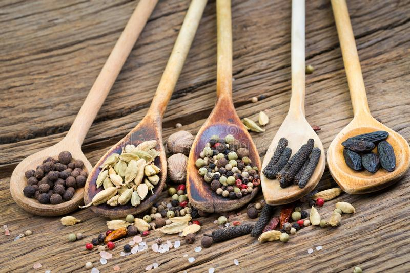 Close up de cinco colheres de cozimento de madeira com as várias especiarias exóticas foto de stock royalty free
