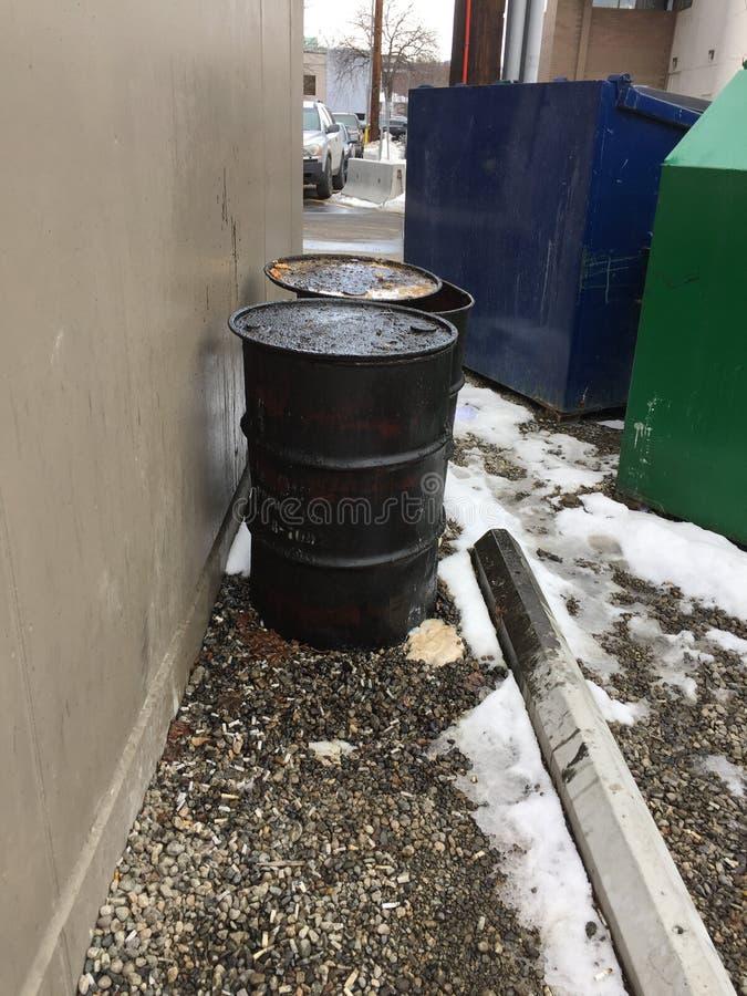 Close up de dois tambores gordurosos sujos fora da construção com o escaninho do lixo e de reciclagem imagem de stock royalty free