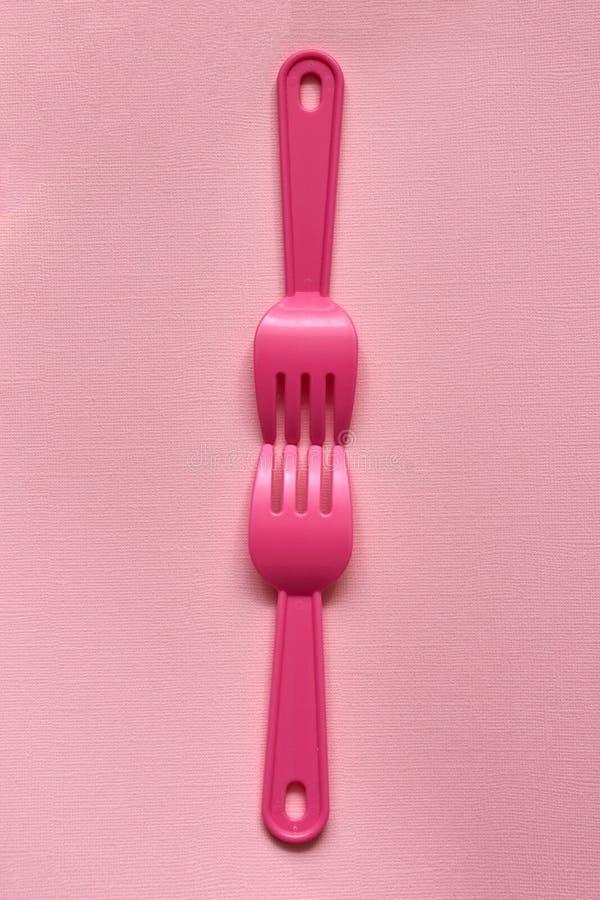 Close-up de duas forquilhas cor-de-rosa plásticas criançolas em um pálido - fundo cor-de-rosa Pratos para um piquenique imagens de stock