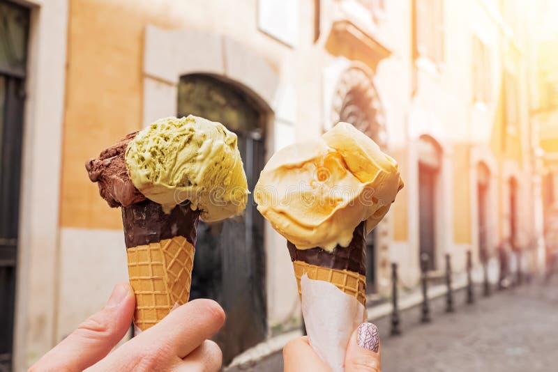 Close-up de duas mãos que guarda cones com o gelato italiano do gelado no fundo do streeet de Roma imagem de stock royalty free