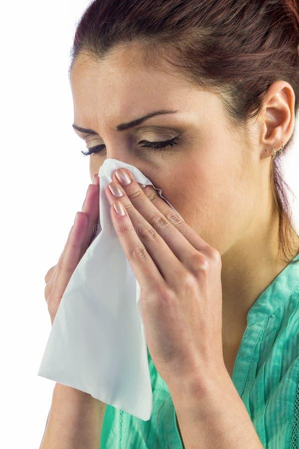 Close-up de espirrar a mulher com os olhos fechados e o tecido na boca foto de stock royalty free