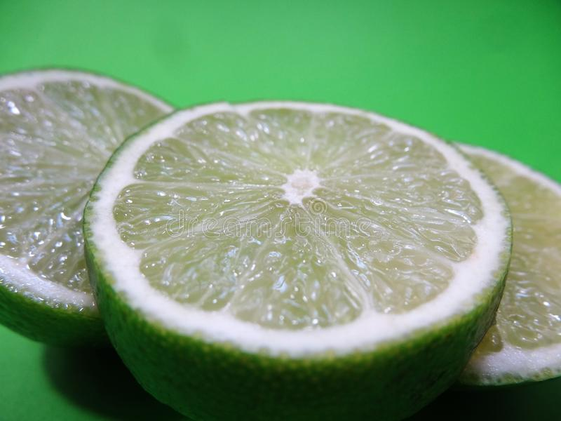 Close up de fatias do limão em um fundo verde fotos de stock royalty free