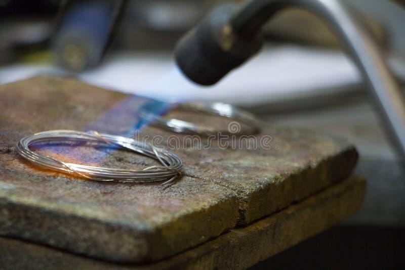Close up de fazer um bracelete feito à mão feito da prata pelo joalheiro mestre fotografia de stock royalty free