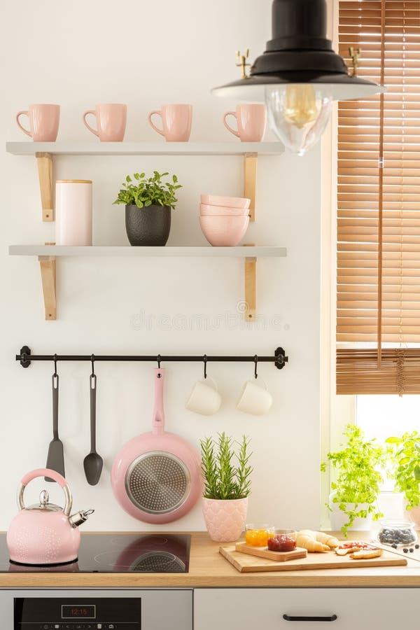 Close-up de ferramentas cor-de-rosa da cozinha, de prateleiras com canecas e da placa de madeira com alimento em um interior da c imagem de stock