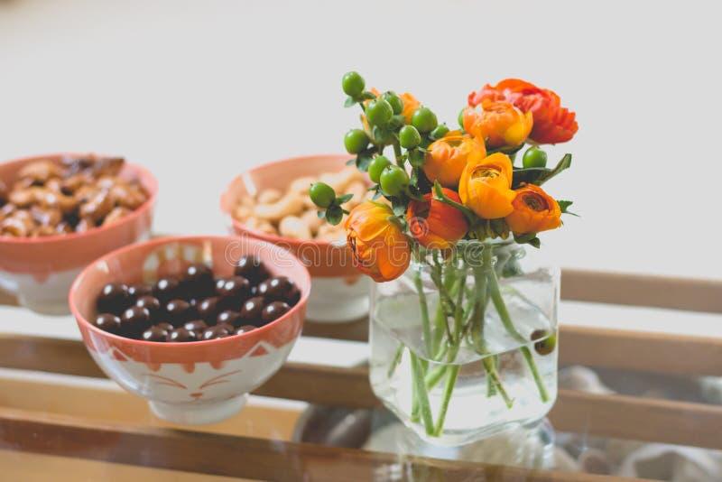Close up de flores coloridas em um frasco de vidro pequeno com tipos de doces diferentes em umas bacias no lado imagem de stock