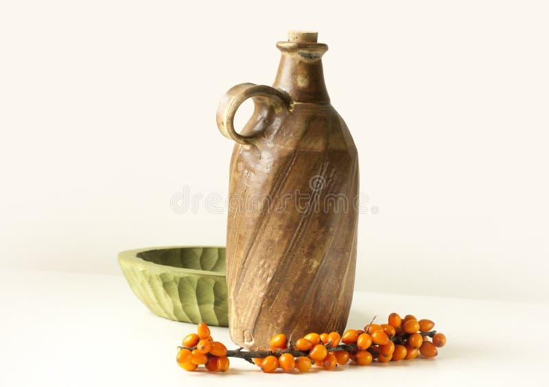 close up de madeira da bacia do frasco da argila das bagas do Mar-espinheiro cerval imagens de stock