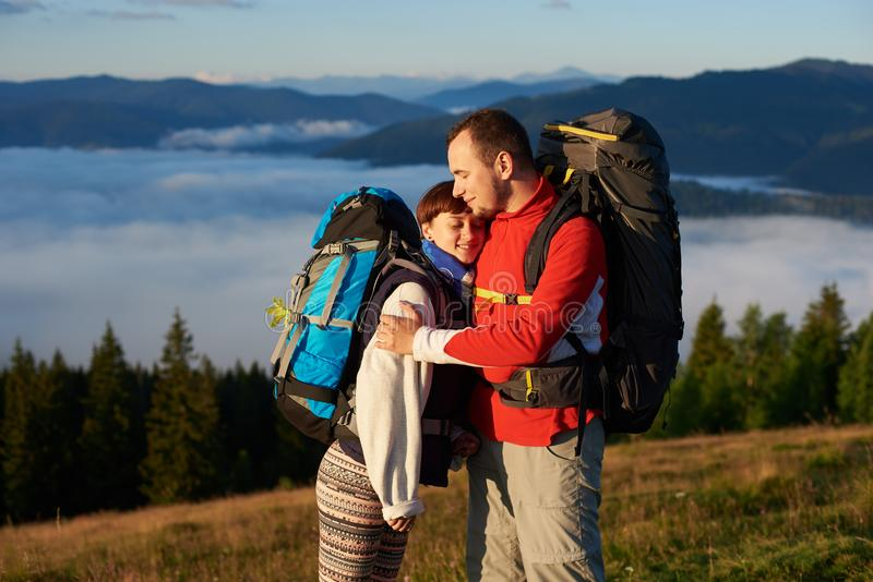 Close-up de masculino e da fêmea que abraçam-se que aprecia raios do por do sol nas montanhas fotografia de stock