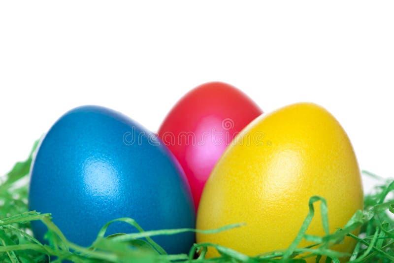 Close-up de ovos de Easter amarelos, vermelhos, azuis no ninho fotos de stock