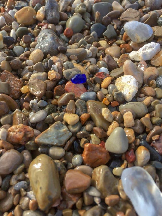 Close up de pedras molhadas coloridas ao longo da linha costeira foto de stock