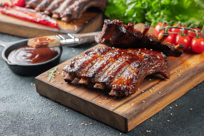 Close up de reforços de carne de porco grelhados com molho do BBQ e caramelizados no mel Petisco saboroso à cerveja em uma placa  imagens de stock
