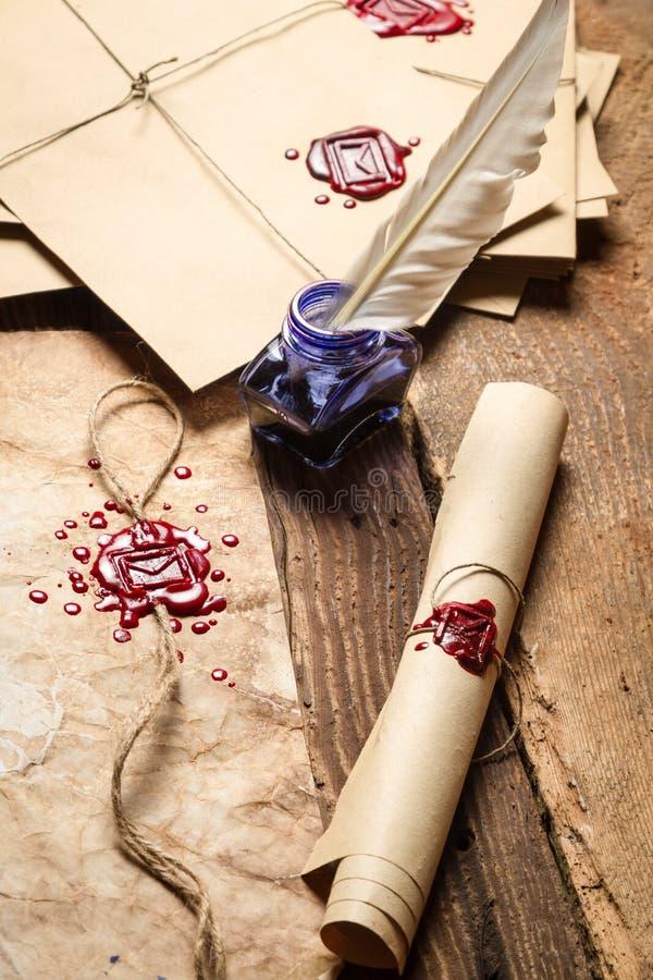 Close up de rolos de papel velhos, de vidros e da tinta azul no inkwe foto de stock royalty free
