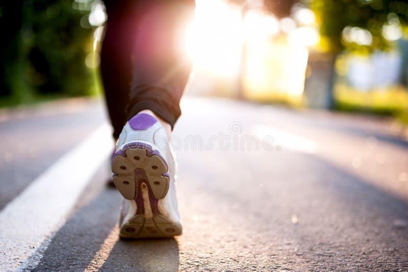 Close-up de sapatas do atleta ao correr no parque Conceito da aptidão fotografia de stock