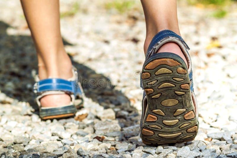 Close-up de sapatas do esporte na fuga que anda nas montanhas em pedras, foto de stock