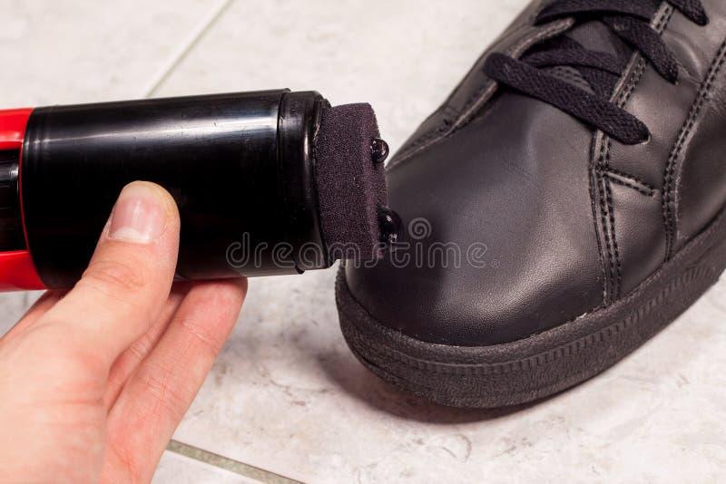 Close up de sapatas do preto da limpeza com pasta preta imagens de stock