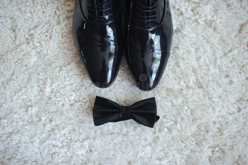 Close-up de sapatas do ` s dos homens e de um laço Tudo no preto fotos de stock royalty free