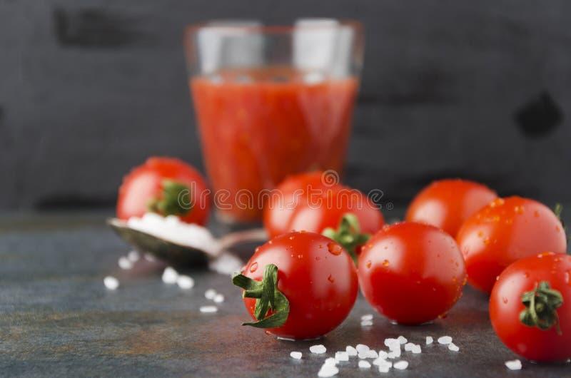 Close up de tomates e do sal frescos de cereja na tabela escura Preparando o suco de tomate caseiro fotos de stock royalty free